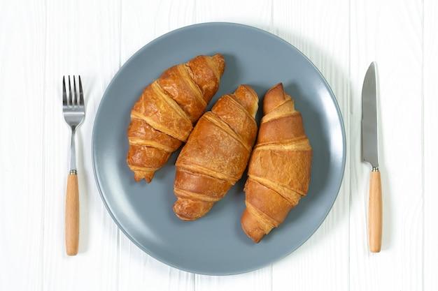 Trois croissants cuits au four sur assiette servis avec une fourchette et un couteau vue de dessus