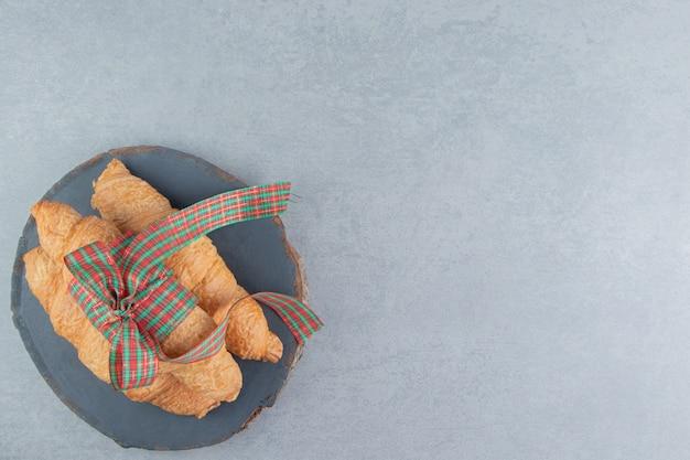 Trois croissants empilés sur le tableau bleu sur le fond de marbre. photo de haute qualité