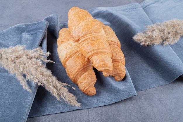 Trois croissants fraîchement sortis du four sur fond gris.