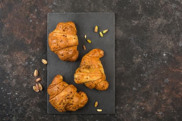 Trois croissants frais garnis de pistache sur un tableau noir avec un fond sombre.