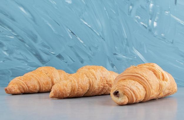 Trois croissants savoureux, sur fond bleu. photo de haute qualité