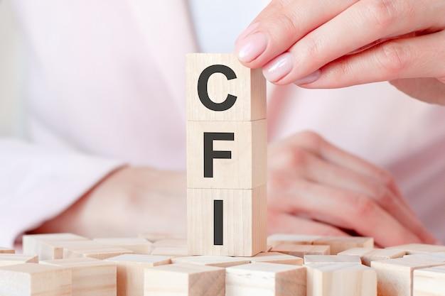 Trois cubes en bois avec des lettres cfi, sur fond de mains féminines en vêtements roses. concept commercial et économique. cfi - intégration d'usine personnalisée
