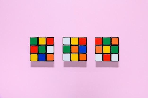 Trois cubes rubiks colorés sur une table rose