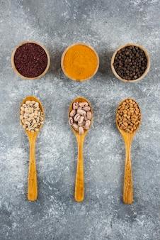 Trois cuillères en bois avec divers haricots sur une table grise.