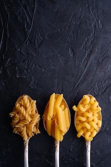 Trois cuillères à couverts avec une variété de pâtes de blé doré non cuites sur fond texturé noir foncé, vue de dessus copie espace
