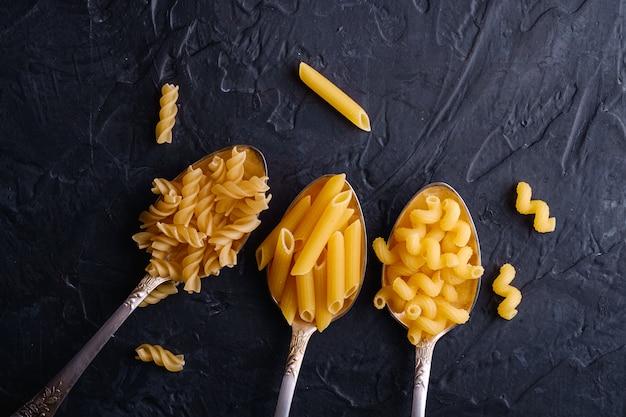 Trois cuillères à couverts avec une variété de pâtes de blé doré non cuites sur fond texturé noir foncé, vue de dessus