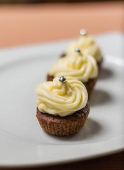 Trois cupcakes au chocolat avec des paillettes d'argent sur le dessus, sur une assiette blanche et une nappe en tissu