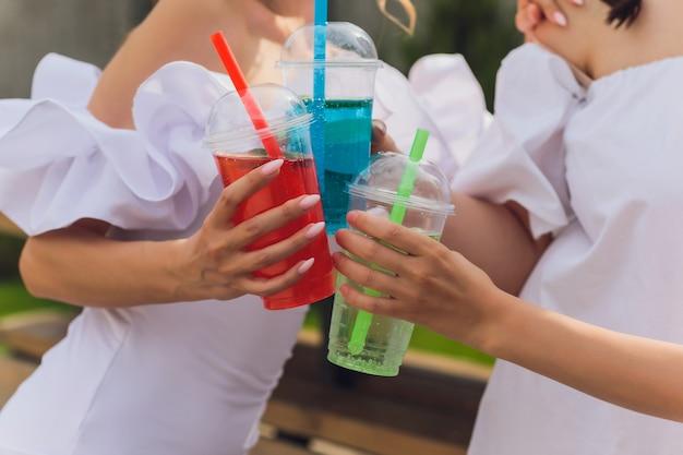 Trois dames acclamant avec de délicieux nectars avec des glaçons avec des pailles noires décoration de palmiers dans une piscine de natation transparente propre eau bleu clair le soleil brille une peau bronzée lisse mode festif sans soucis