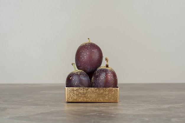 Trois délicieuses prunes placées sur une surface en marbre