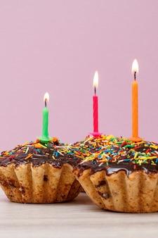 Trois délicieux cupcakes d'anniversaire avec glaçage au chocolat et caramel, décorés de bougies festives allumées sur fond lilas. concept minimal de joyeux anniversaire.