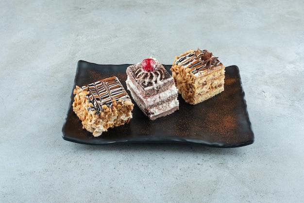 Trois délicieux gâteaux sur plaque noire. photo de haute qualité