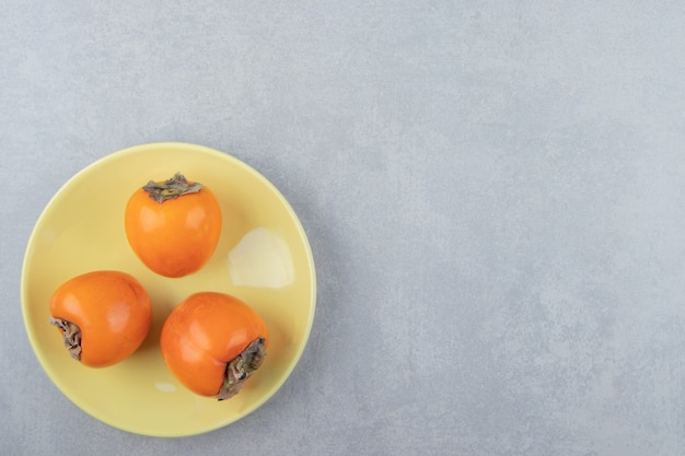 Trois délicieux kakis sur plaque jaune