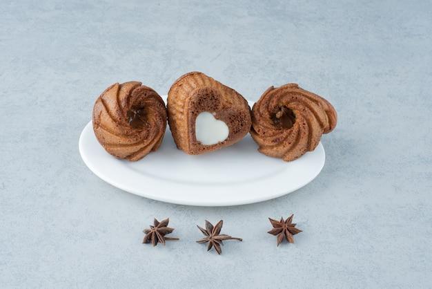 Trois délicieux petits gâteaux sur plaque blanche. photo de haute qualité