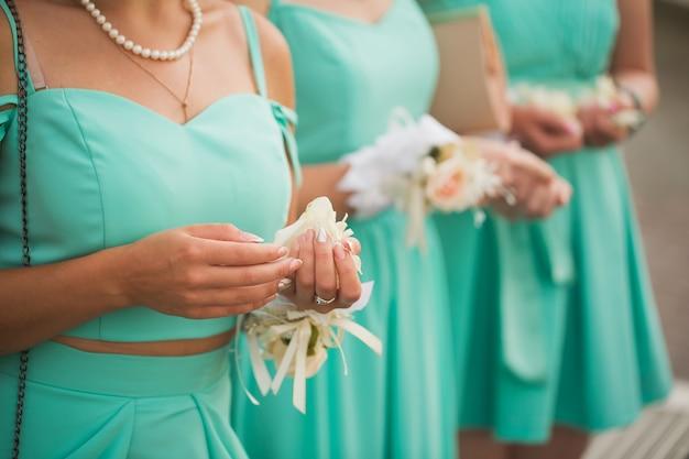 Trois demoiselles d'honneur tenant un bouquet de mariée en mains