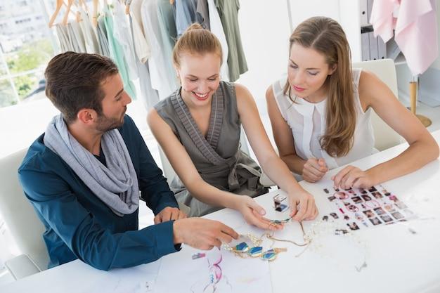 Trois designers de mode discutant des dessins