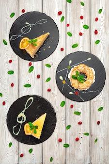 Trois desserts servis sur des assiettes noires sur la vue de dessus de table en bois