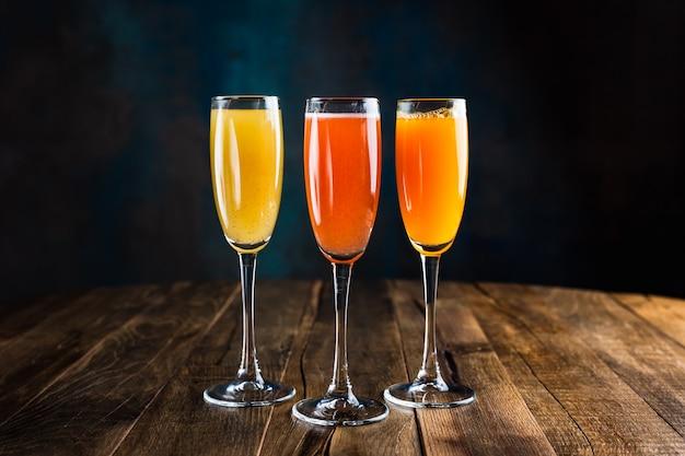 Trois différents cocktails fruités pétillants, rouges, jaunes et orange, dans des verres à flûte