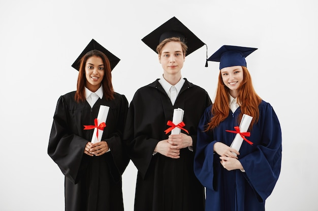 Trois diplômés heureux souriant détenant des diplômes.