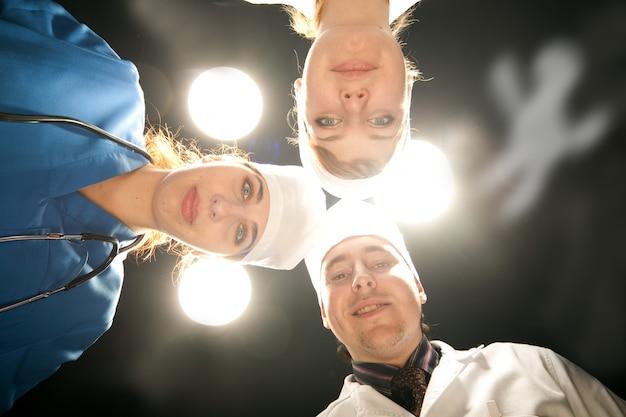 Trois docteurs en opérations avec lampe blanche