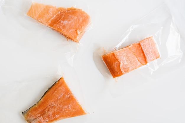 Trois emballages de filets de poisson au saumon congelés dans de petits sacs en plastique emballage sous vide steaks de poisson rouge cru