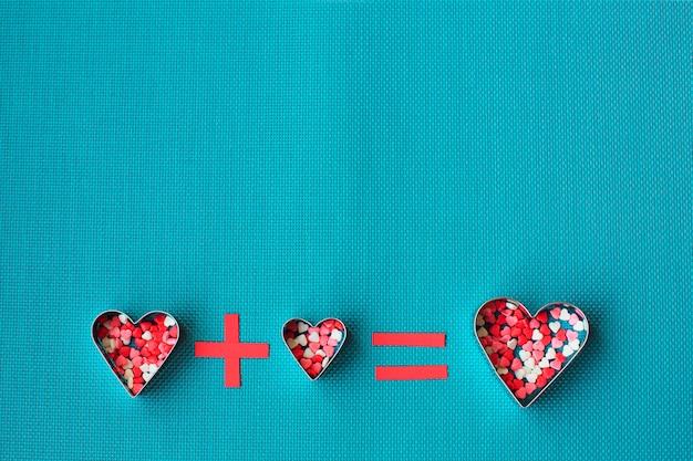 Trois emporte-pièces en forme de coeur sur un bleu.