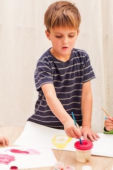 Trois enfants apprennent à peindre avec un pinceau et des aquarelles sur papier à la maternelle
