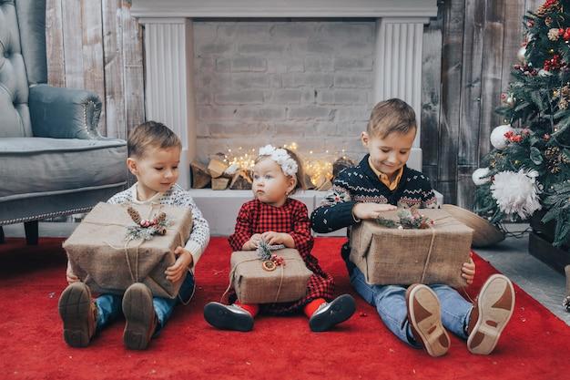 Trois enfants avec des cadeaux de noël