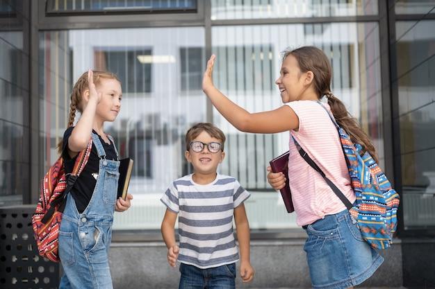 Trois enfants caucasiens mignons et heureux avec des lunettes et un sac à dos se tiennent debout et parlent ensemble, en donnent cinq dans la cour d'école. vacances. intello. journée du savoir. fermer. retour au concept de l'école.