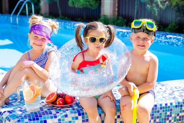 Trois enfants en été s'assoient au bord de la piscine avec des lunettes de soleil et boivent de la limonade
