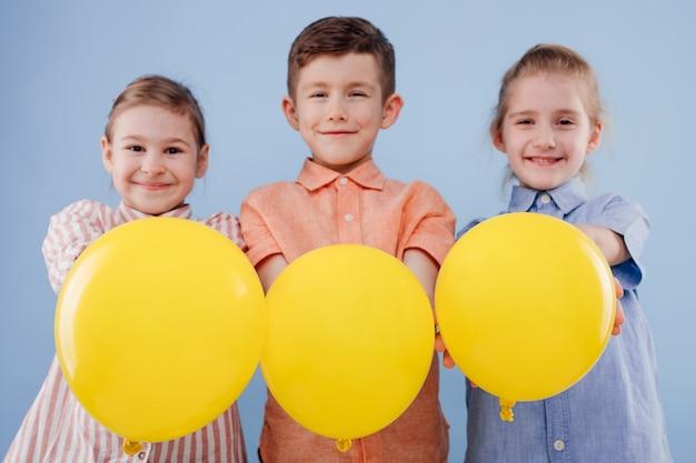 Trois enfants heureux fille et garçon avec ballon jaune avec sourire regardent la caméra isolée sur bac bleu...