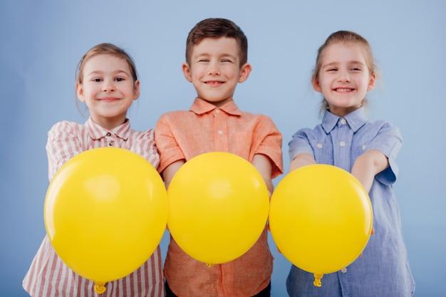 Trois enfants heureux filles et un garçon avec des ballons jaunes avec un sourire regardent la caméra isolée o...