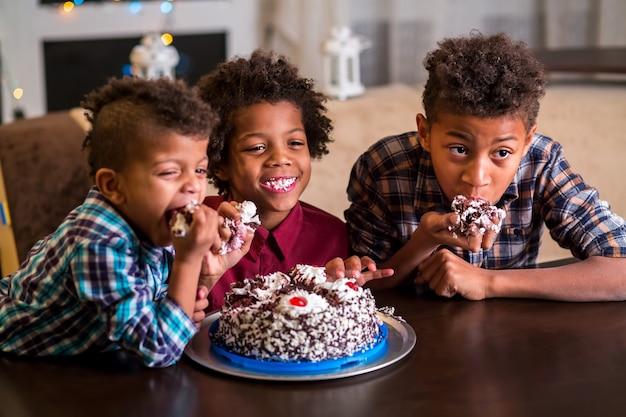 Trois enfants mangeant un petit gâteau.