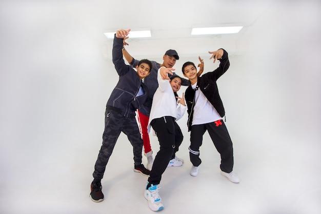 Trois enfants sautant et dansant d'entraîneur isolés sur fond blanc. portrait de danseur enfant sautant en studio.