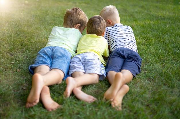 Trois enfants sont allongés sur le ventre sur l'herbe verte du parc en été, communiquent, jouent