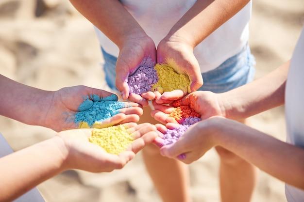 Trois enfants tenant de la poudre colorée dans les mains