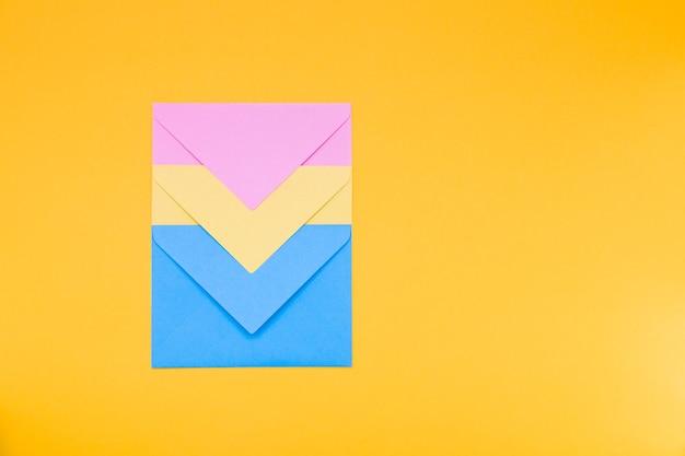 Trois enveloppes sur un fond jaune vue de dessus de l'espace de copie