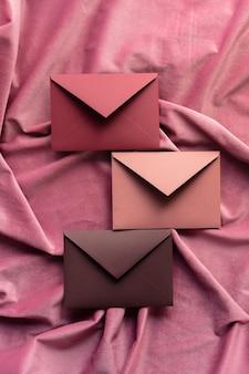 Trois enveloppes sur tissu bordeaux, vue de dessus
