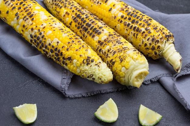Trois épis de maïs grillés sur serviette grise. tranches de citron vert sur la table. fond noir.