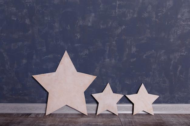 Trois étoiles de bois sur un mur.