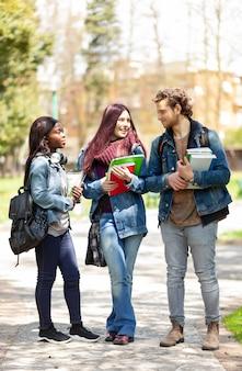 Trois étudiants dans le parc en plein air.