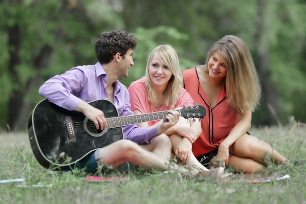 Trois étudiants avec une guitare assis sur l'herbe dans le parc de la ville.