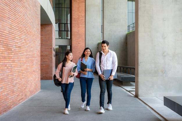 Trois étudiants marchent et parlent ensemble dans la salle universitaire