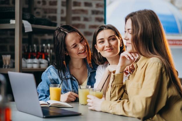 Trois étudiants se préparant à l'examen avec un ordinateur portable dans un café