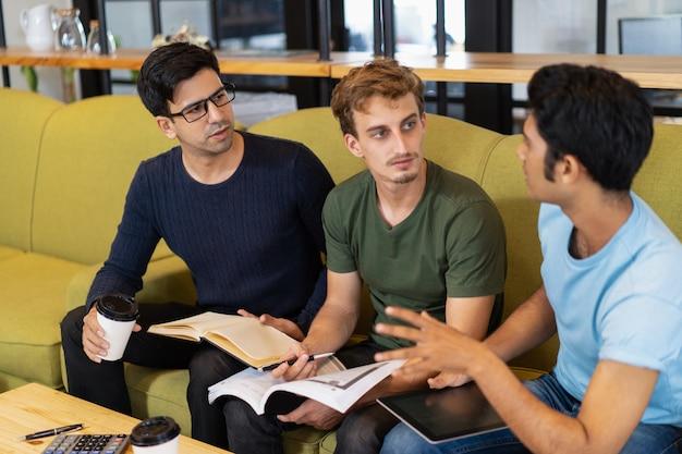 Trois étudiants sérieux discutant des devoirs