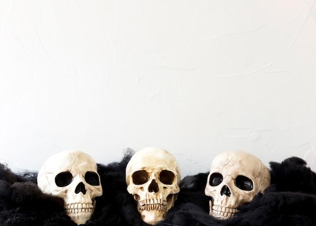 Trois faux crânes sur un matériau mou