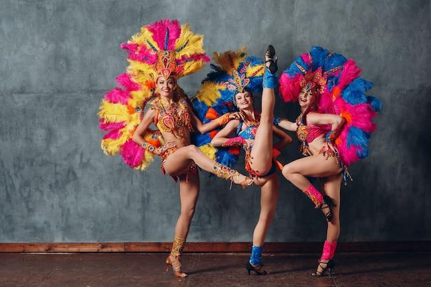 Trois femme en costume de cabaret avec plumage de plumes colorées.