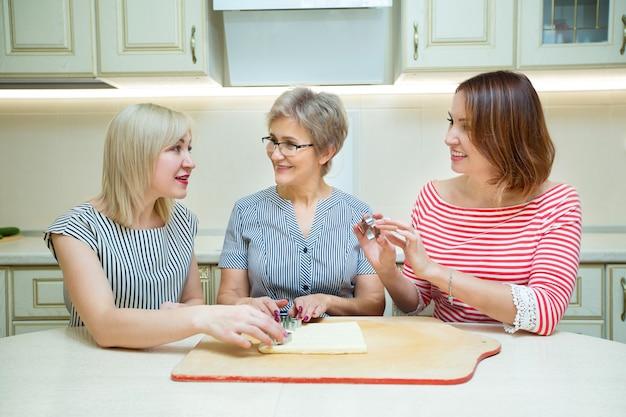 Trois femmes adultes élégantes faisant des biscuits dans la cuisine