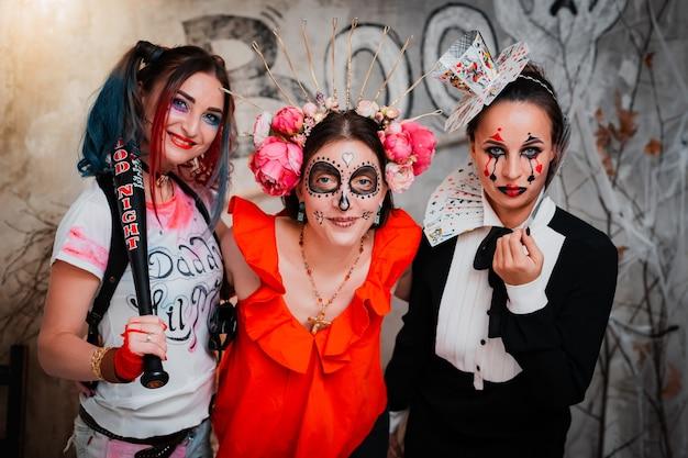 Trois femmes amies avec un maquillage effrayant célébrant ensemble les vacances d'halloween