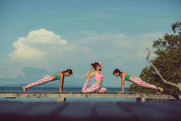 Trois femmes asiatiques jouant yoga flow sur la jetée de la plage