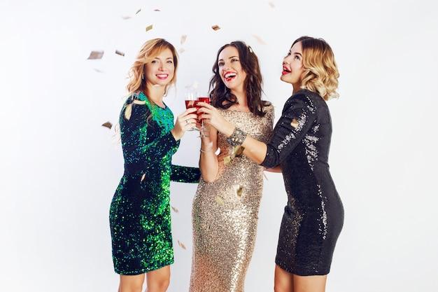 Trois femmes célébrant en tenue de soirée scintillante profitant du temps ensemble, buvant du vin et dansant. fond blanc.